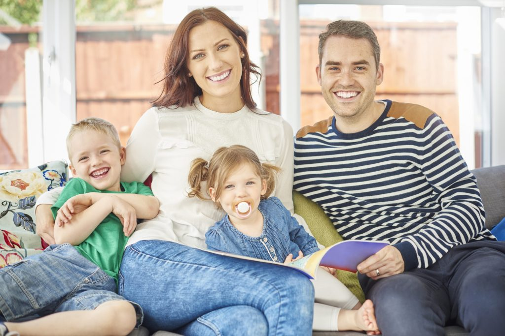 A 2 year old girl and four year old boy are sitting with their mother and father and reading a picture book together . they are on a sofa in a conservatory of a modern house. The little girl is really enjoying the picture book , laughing along with mum . The little girl is sucking a dummy pacifier and they are all smiling to camera .