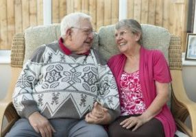 A mature couple sit together hand in hand on the sofa in their conservatory. They are a real couple and looked relaxed and content together.